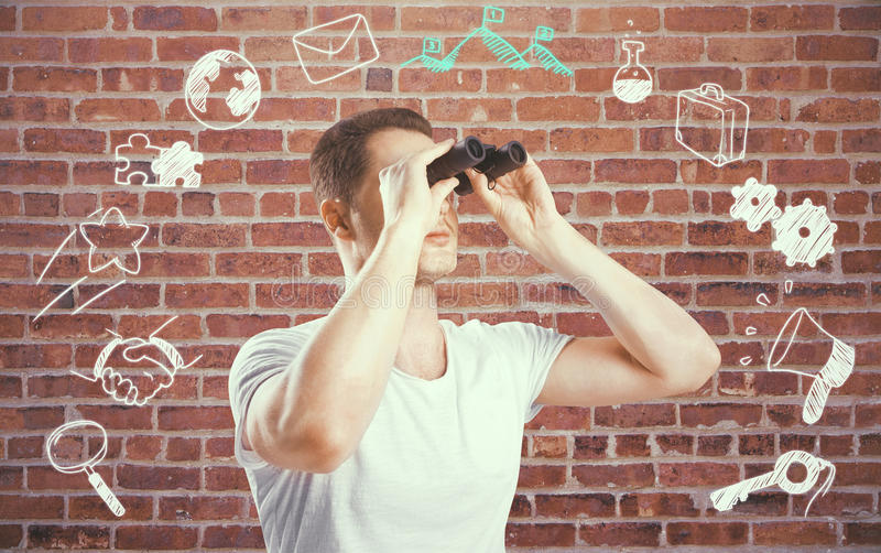 Man with binoculars and business icons. Young european man with binoculars and business icons on red brick wall background. Success concept stock images