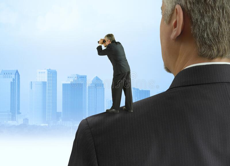 Man with binoculars looking into the distance standing on the shoulders of giants concept with cityscape background royalty free stock photo