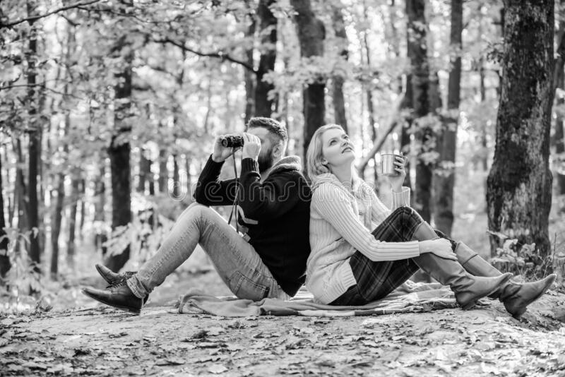 Man with binoculars and woman with metal mug enjoy nature park. Park date. Relaxing in park together. Happy loving royalty free stock photography