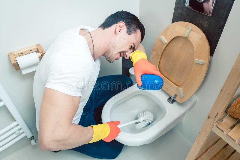 Man is a bit disgusted cleaning the toilet. With brush royalty free stock photography