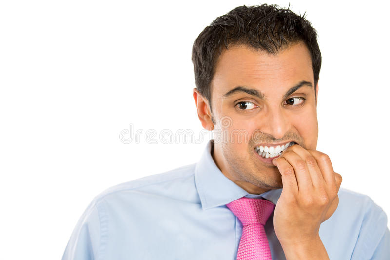 Man biting his nails and looking to the side with a craving for something or anxious. Closeup portrait of a man biting his nails and looking to the side with a stock image