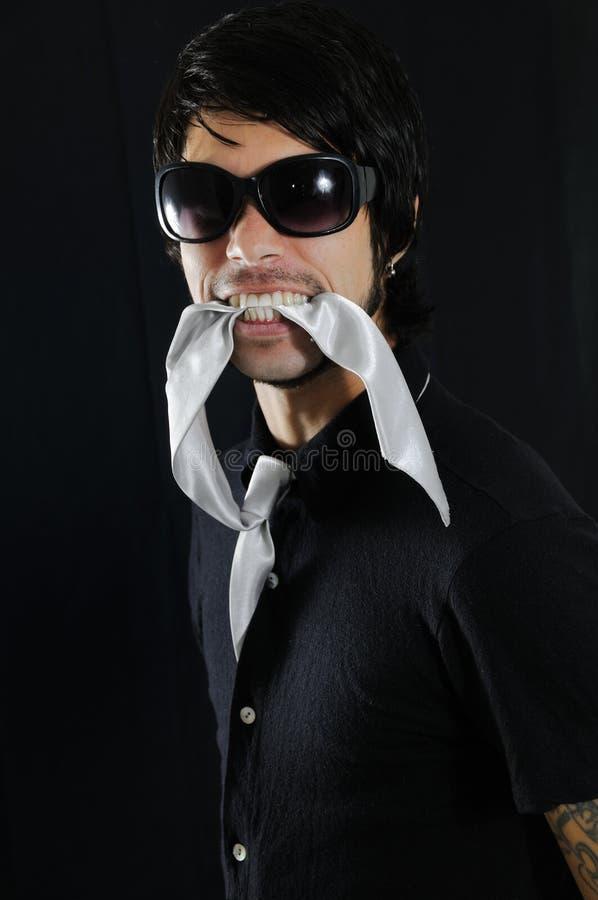 Man biting his tie stock image