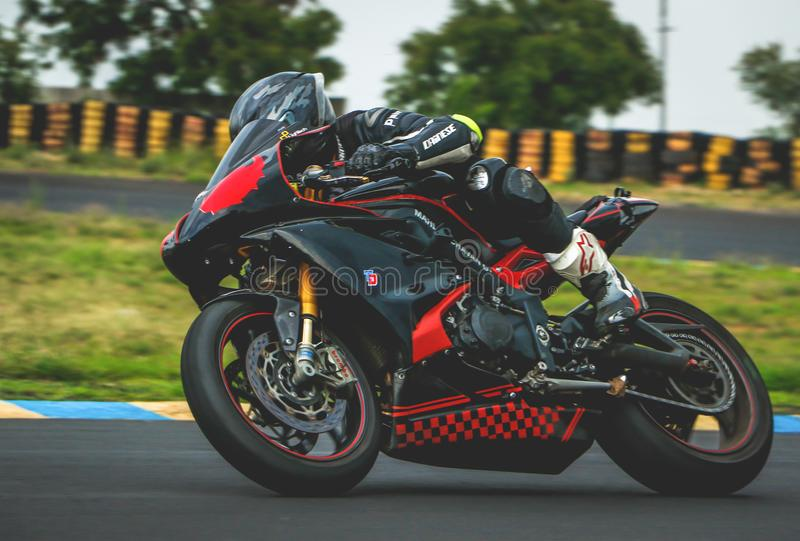 Man With Black Alpinestar Racing Suit Riding Black and Red Sports Bike stock image