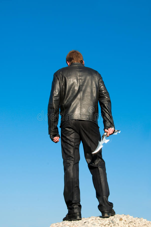 Man in black with an antique knife. Man in black on a rock with an antique knife stock images