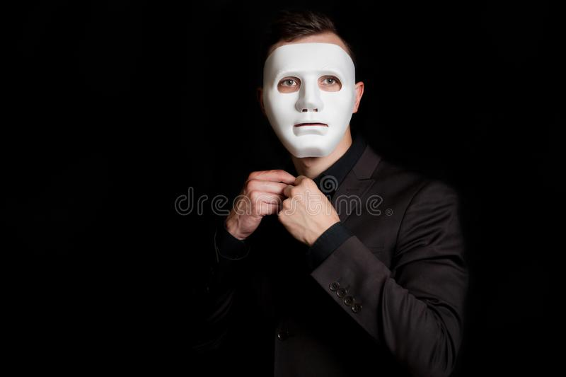 A man on a black background in a white mask. Button a button on his shirt.  royalty free stock image