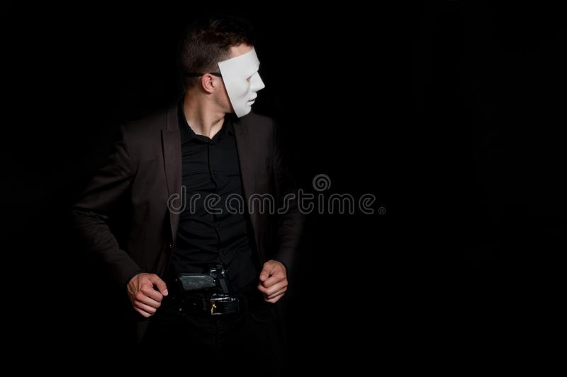 A man on a black background in a white mask. With a gun in your pants.  stock photography
