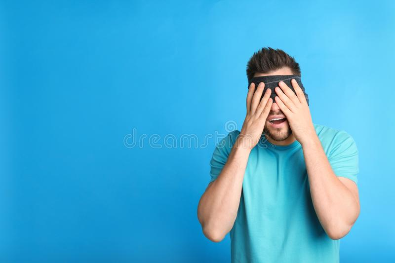 Man with black blindfold on blue background royalty free stock photo