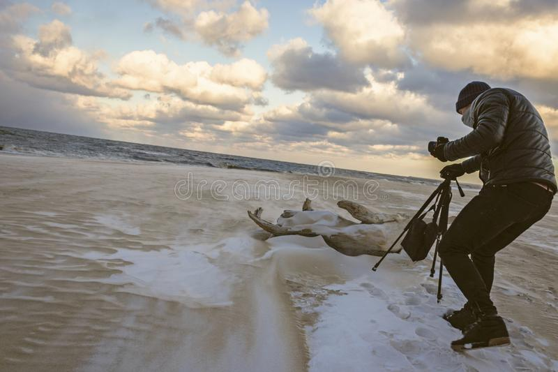 Man in Black Bubble Jacket Walking on Seashore While Holding Black Camera Tripod royalty free stock image