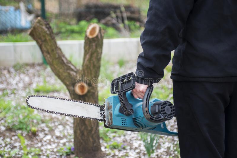 Man in black clothes hold blue chainsaw with his bare hands.  stock photos