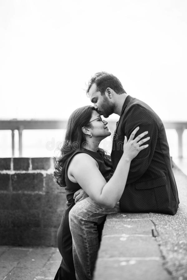 Man In Black Coat Sitting While Kissing Woman royalty free stock images