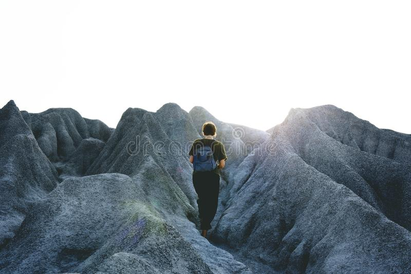 Man in Black Crew Neck Shirt and Pants Walking on Gray Mountain Formations stock images