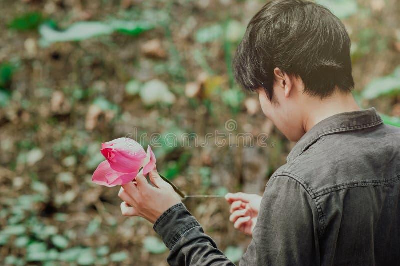 Man in Black Denim Jean Holding Pink Flower stock image