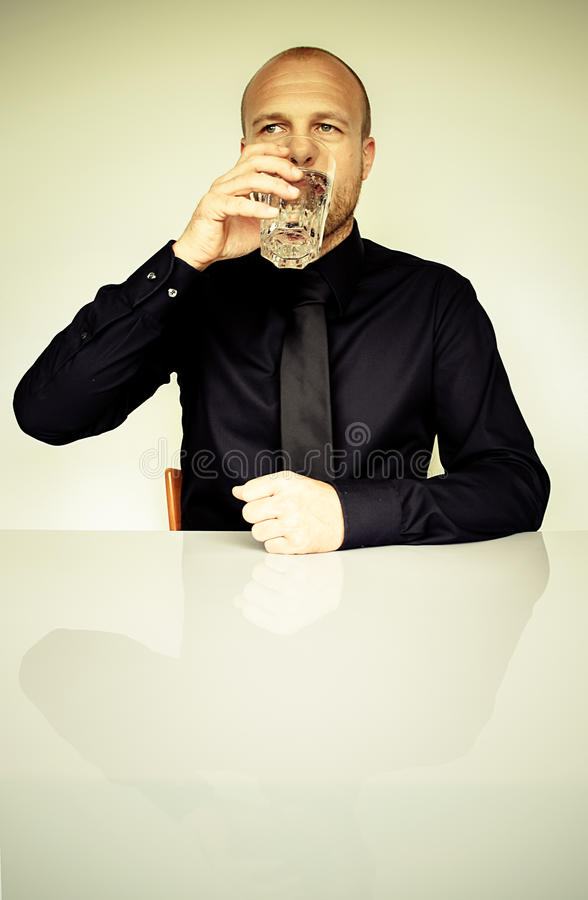 Man in Black Dress Shirt Sitting in Front of White Table Drinking Water stock photos
