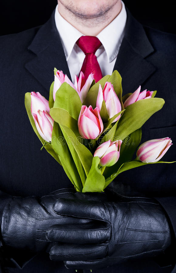 Man in black with flowers stock photo