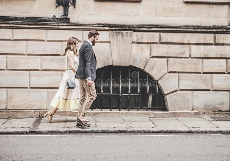 Man in Black Formal Suit Jacket Walking Together With Woman in White Sleeveless Dress stock images
