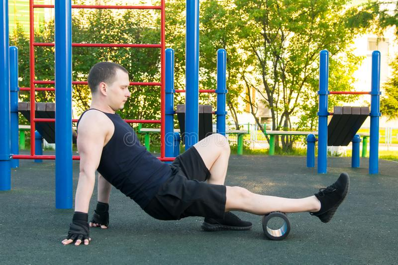 Man in black gloves, outdoors, doing sports and doing roller massage, calf muscle royalty free stock image