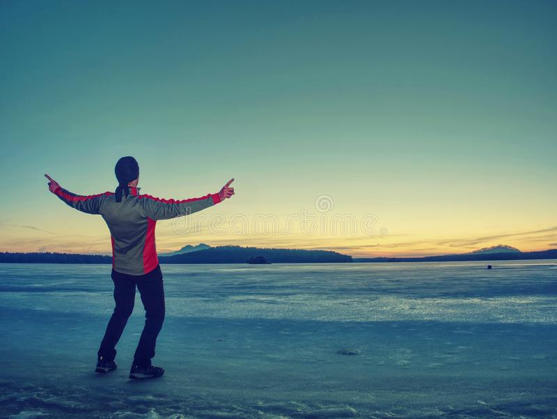 Man in black gray jacket on ice looking over frozen lake. The ice desert frozen lake, winter, wind, trekking, traveler, tourists, tourism, sunshine, sunrise stock image