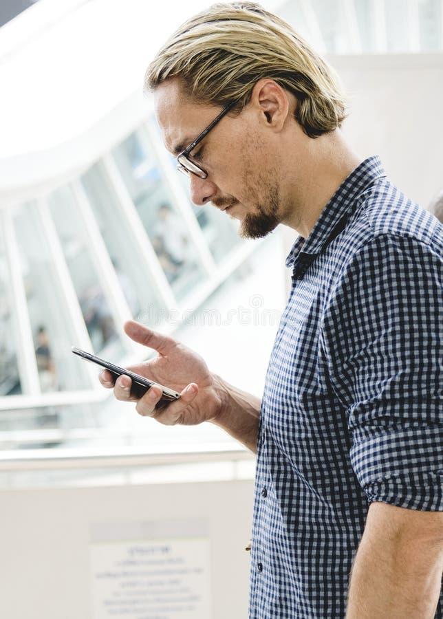 Man in Black and Gray Tattersall Dress Shirt Holding Smartphone stock photo