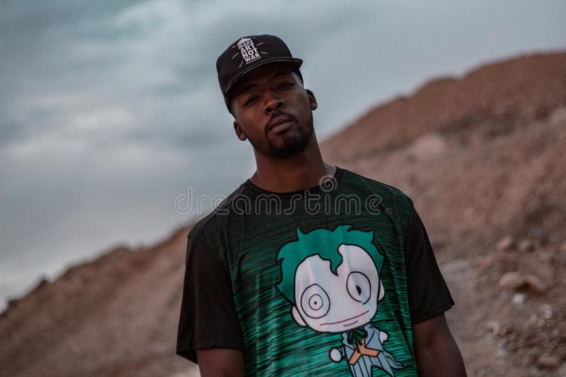Man in Black and Green Crew-neck T-shirt Standing on Mountain Selective Focus Photography royalty free stock images