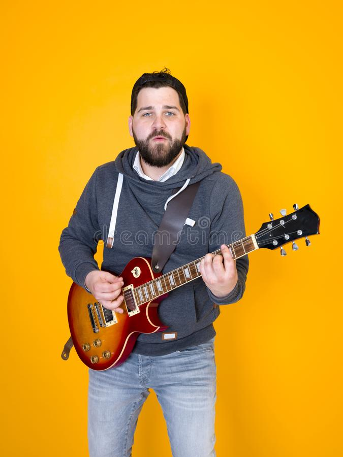 Man with black hair and beard, wearing grey hoodie playing the electric guitar in front of a yellow background stock photo