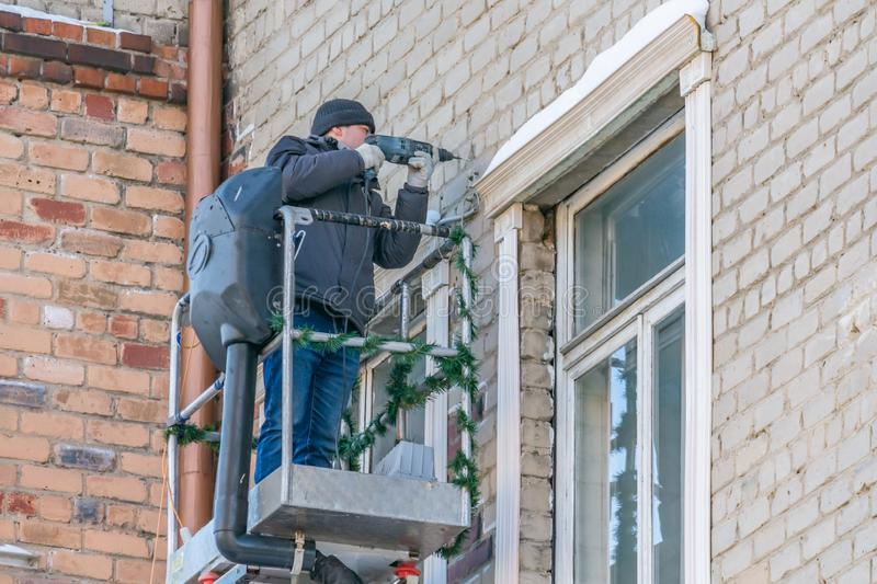Yekaterinburg, Sverdlovsk / Russia - 02 12 2018: A man in black hat and white working gloves and a black jacket and blue trousers royalty free stock image