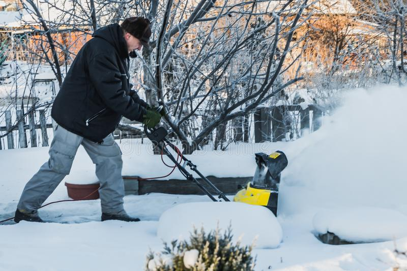 A man in a black jacket and a gray pants is brushing white snow with the yellow electric snow thrower in winter stock photo