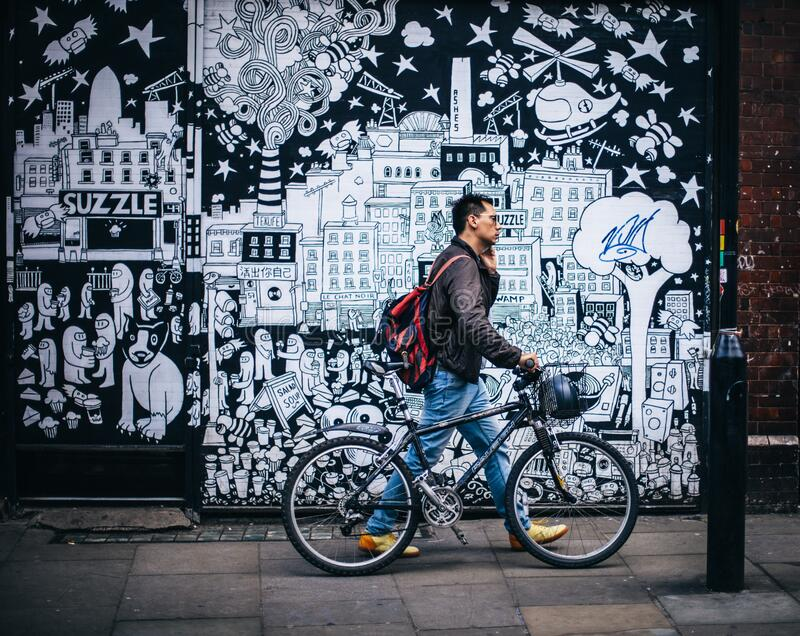 Man In Black Jacket Holding A Black Hardtail Bike Near Black And White Art Wall Free Public Domain Cc0 Image