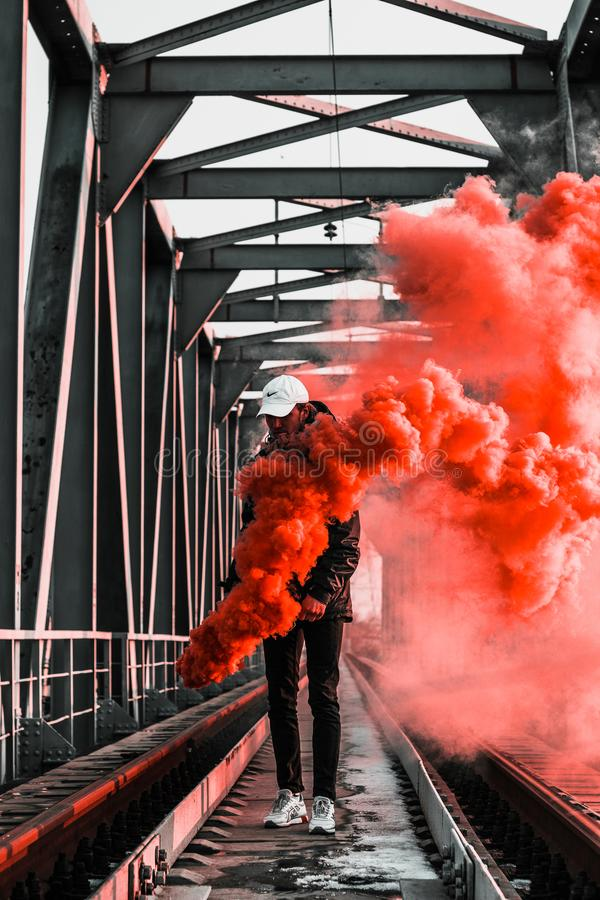 Man in Black Jacket Holding Red Smoke on Metal Bridge royalty free stock images