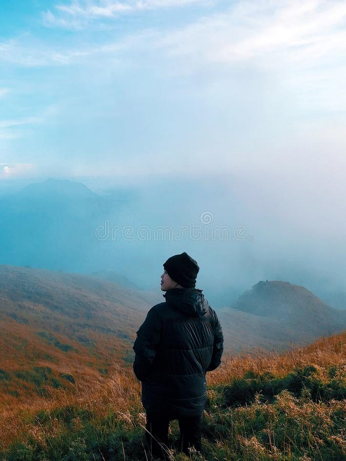Man in Black Jacket Standing on Mountain With Fog stock image