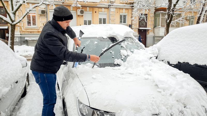 Shot of man in black jacket trying to clean up car from snow with brush against the house royalty free stock photos