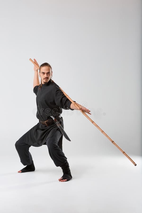 A man, in a black kimono is practicing martial arts technique with a long bamboo fighting stick. royalty free stock photos