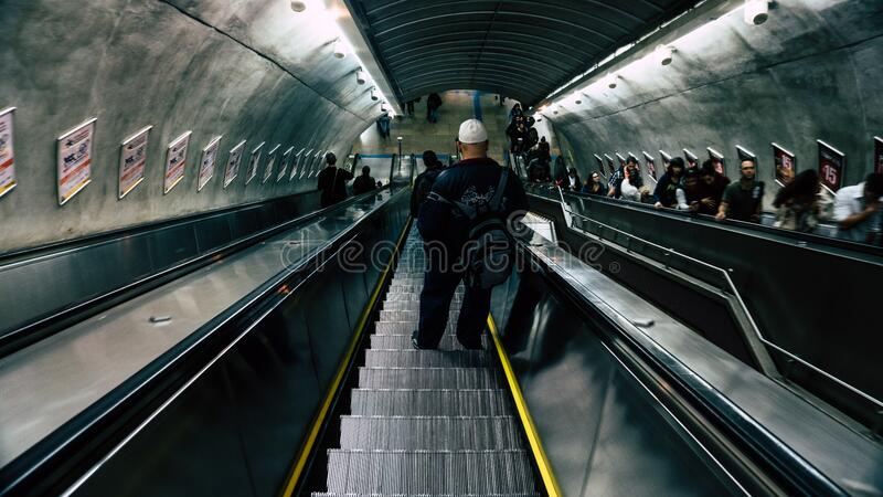 Man in Black Leather Jacket on Escalator royalty free stock photography
