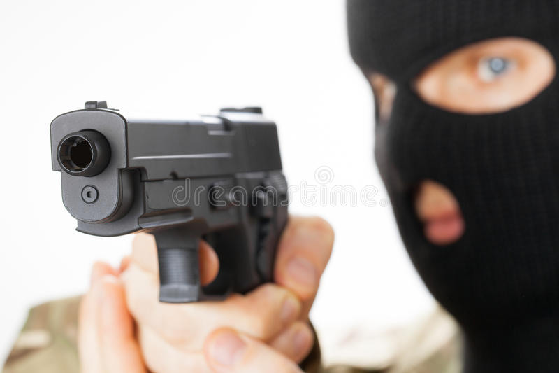 Man in black mask holding gun in front of him. Studio shot stock photography