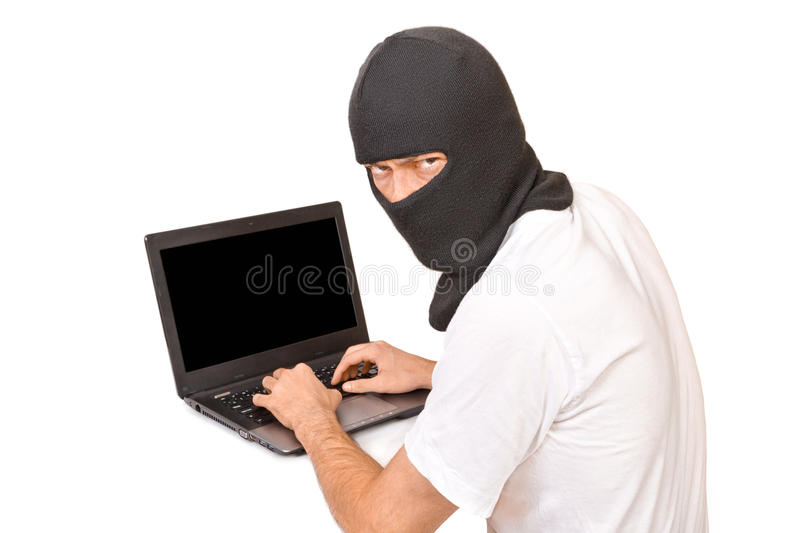 Man in black mask looking at camera and typing something. Man in black mask looking at camera with evil view and typing something royalty free stock images