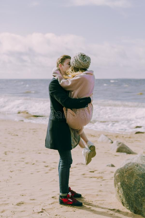 Man in Black Overcoat and Blue Denim Jeans Kissing While Carrying a Woman in Pink Overcoat and Knit Cap on Shore at Daytime royalty free stock photos