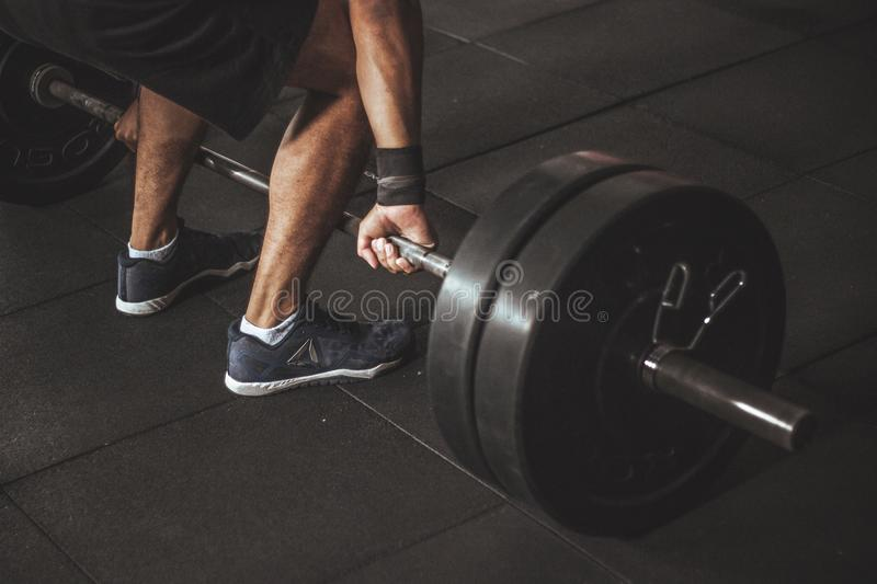 Man in Black Reebok Shoes About to Carry Barbell royalty free stock image