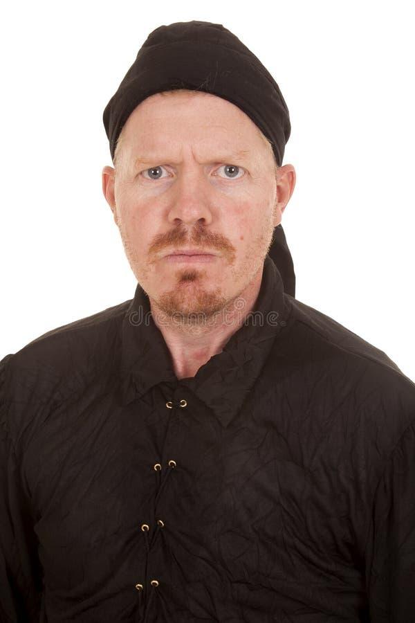 Man black shirt and bandana serious. A mad man in a bandana with a black shirt royalty free stock image