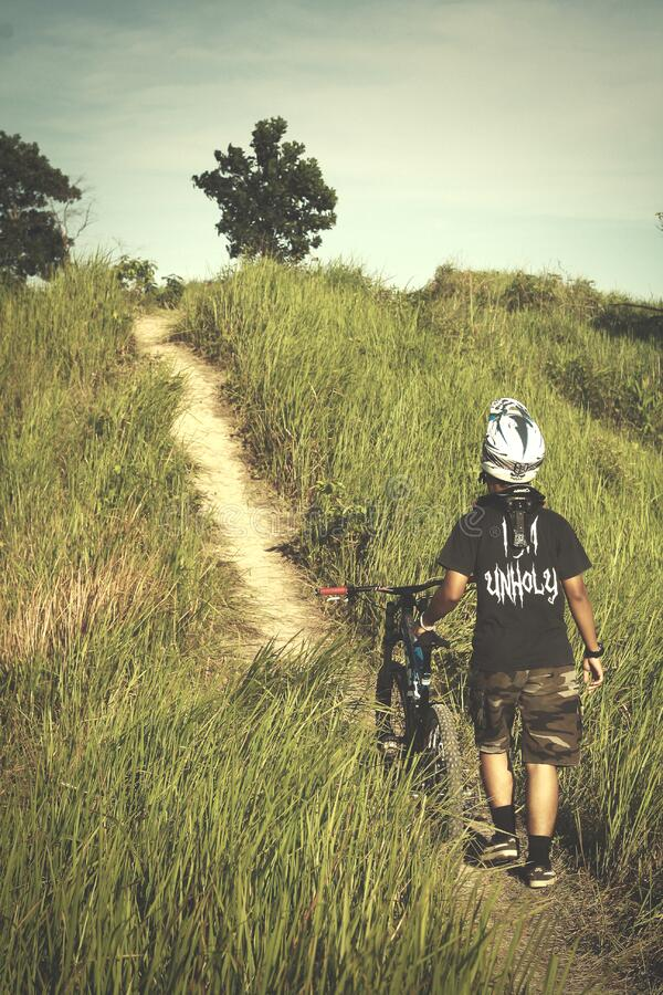 Man in Black Shirt and Brown Shorts Holding Bicycle royalty free stock images