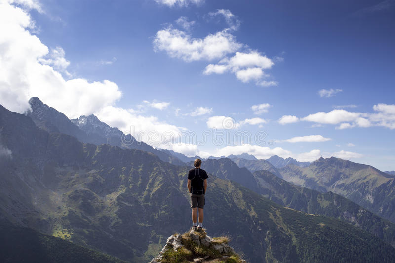 Man In Black Shirt And Gray Shorts Standing On Cliff Under White And Blue Cloudy Sky Free Public Domain Cc0 Image