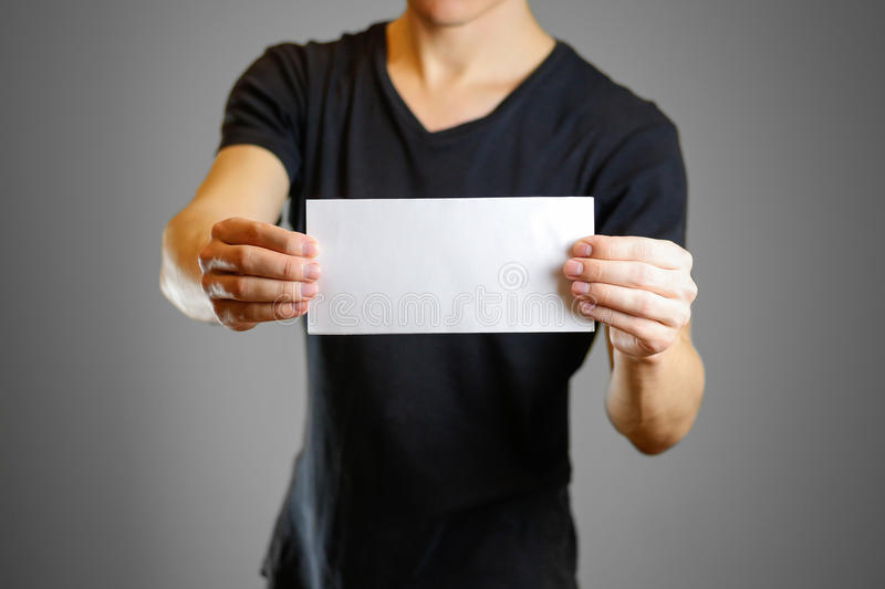 Man in a black shirt holding a white sheet of paper. Empty flyer.  stock photos