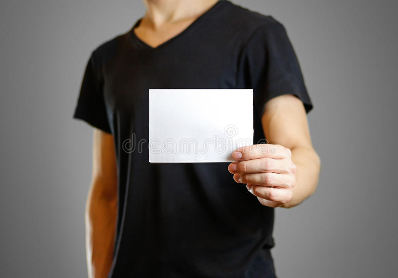 Man in a black shirt holding a white sheet of paper. Empty flyer.  royalty free stock photos
