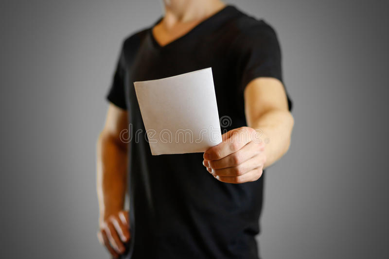 Man in a black shirt holding a white sheet of paper. Empty flyer.  royalty free stock photo