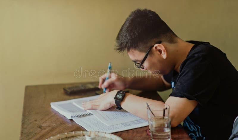 Man in Black Shirt Sitting and Writing stock image
