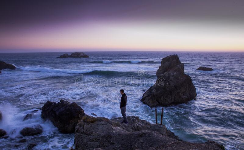 Man in Black Shirt Standing on Rock in Between Sea Water royalty free stock image