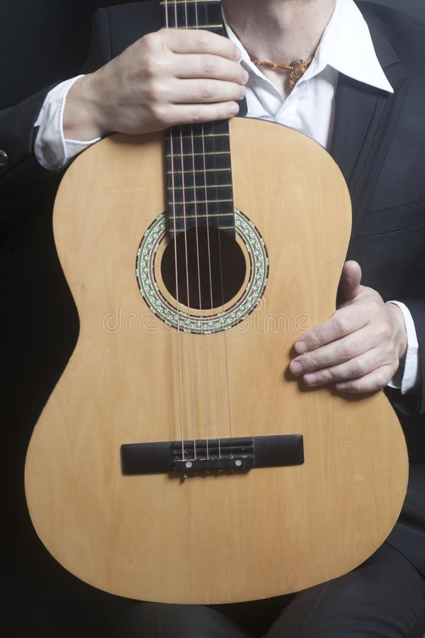 Man in black suit with acoustic classic guitar stock photo