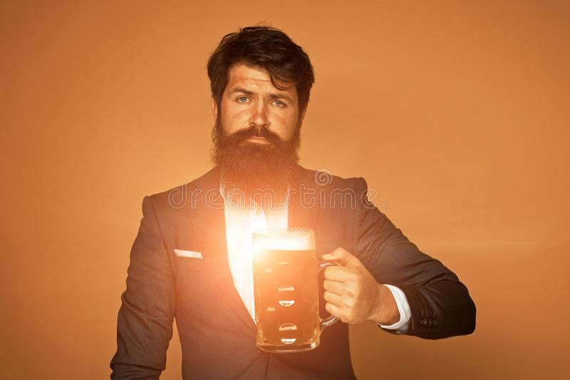 Man in black suit with a glass of beer. Happy elegant man drinking beer. Beer pubs and bars. Bearded man drinking lager stock image