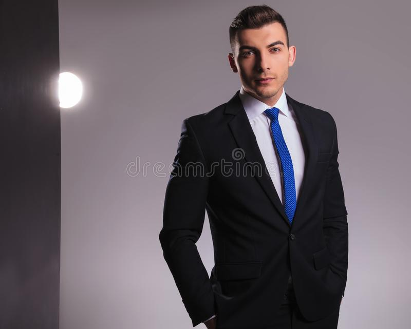 Man in black suit with hands in pockets stock photo