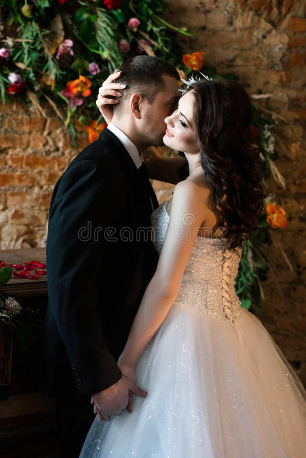 Man in a black suit kissing his woman stock photos