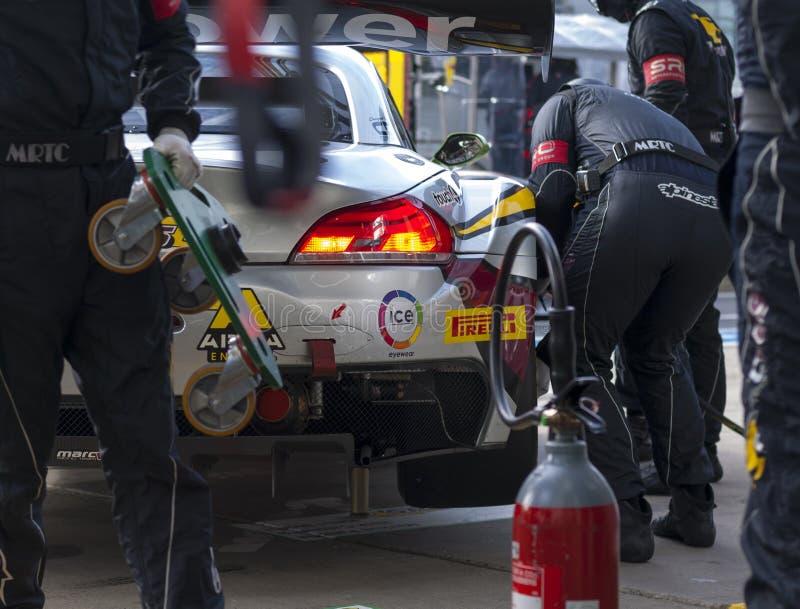 Man in Black Suit Repairing Grey Car royalty free stock image