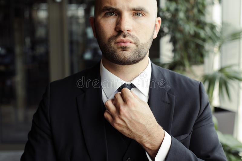 A man in a black suit straightens his tie stock image